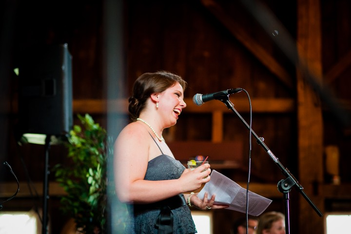 Maid of honor gives funny speech during a barn wedding reception