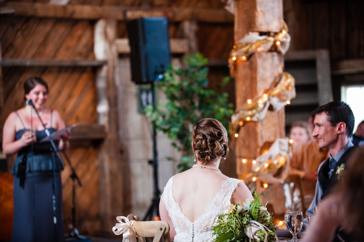 Bride and groom enjoy the toasts during their barn wedding reception