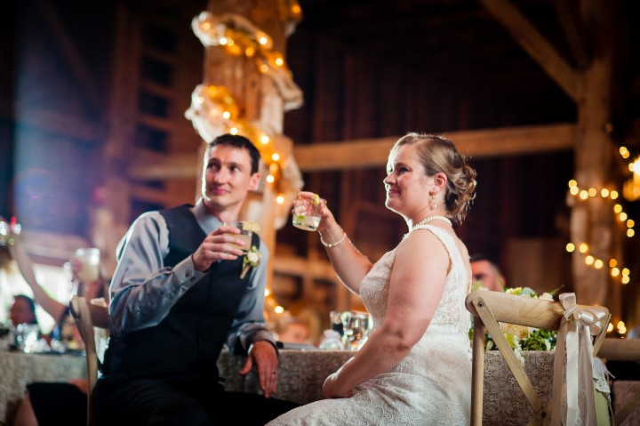 bride and groom cheers after the toasts are complete  during their wedding reception