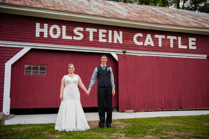 Bride and groom pose in front of old cattle barn during their rustic wedding reception