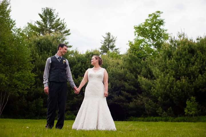 bride and groom stand a meadow for a portrait
