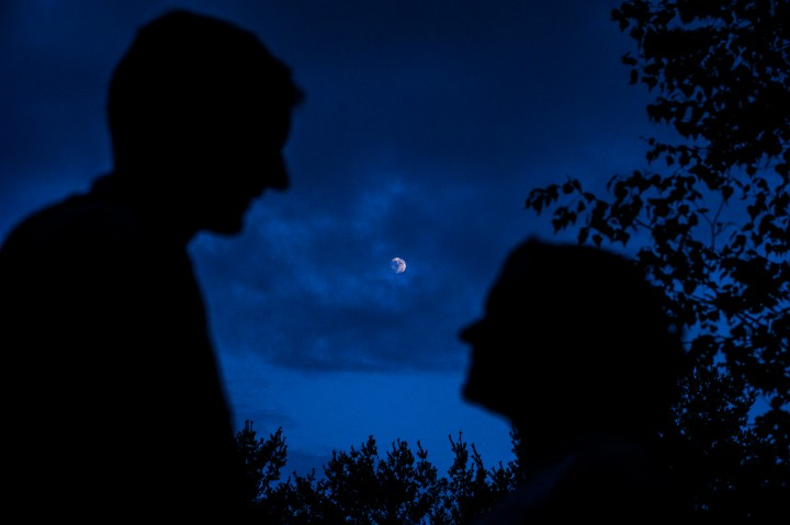 Silhouette of bride and groom with the moon behind them at dusk