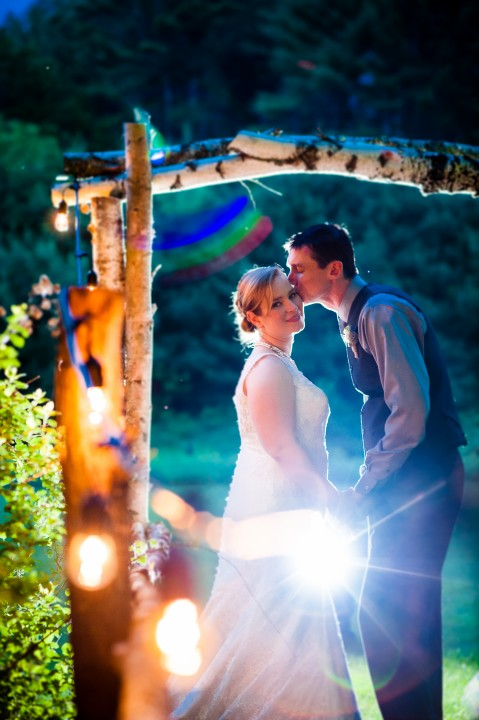 lights and a birch arbor surround the bride and groom