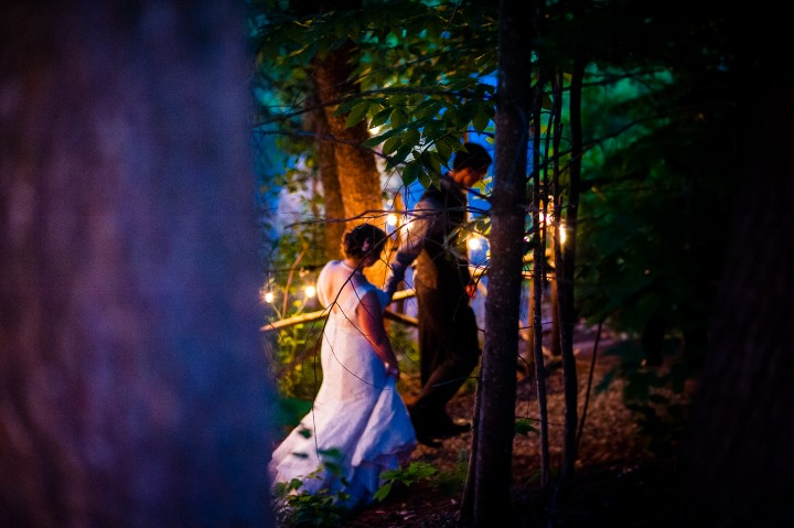groom leads his beautiful bride down a christmas tree light wooded path