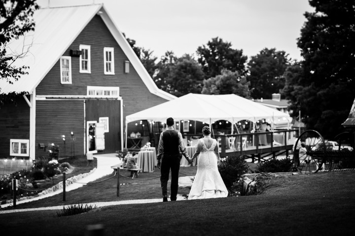 bride and groom hold hands and walk back to reception barn
