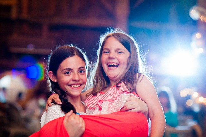 two girls pose for a picture during a barn wedding reception
