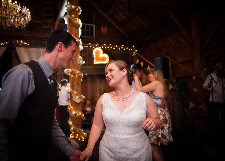 bride and groom dancing with a heart behind them during their barn wedding reception