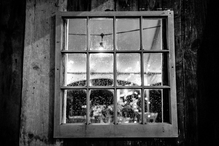 rain coats the windows of the barn during a wedding reception