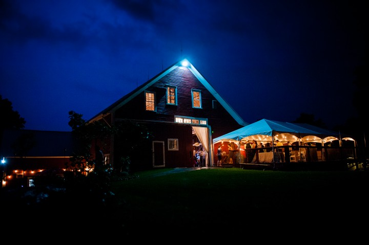 lightning lights up the sky behind the barn during bride and grooms wedding reception