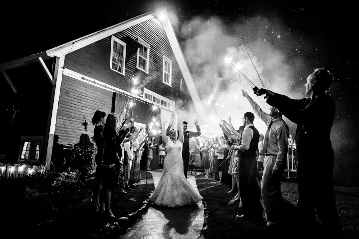 Bride and groom run out of the barn for their sparkler exit at the end of their wedding reception