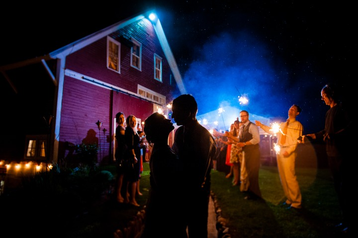 bride and groom kiss with sparklers in the background during their barn wedding reception sparkler exit