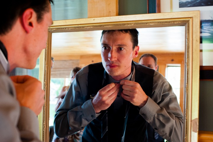 handsome groom buttons collar in the mirror before his rustic barn wedding