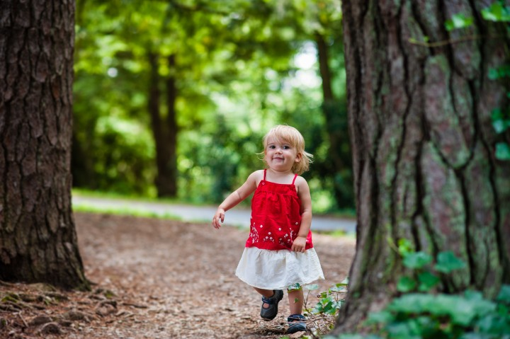 little blonde girl runs down wooded path