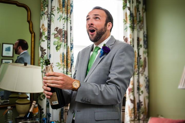 handsome groom during his omni mount washington wedding pops some champagne in celebration