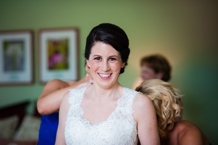 gorgeous bride gets into her gown before her mountain wedding ceremony