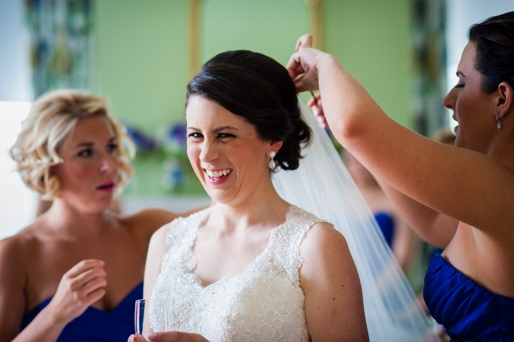 Beautiful smiling bride and her girls putting her veil in before her luxury mountain wedding