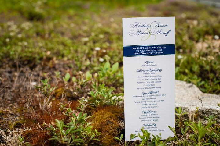 White and blue wedding ceremony programs rest on the mountain vegeation