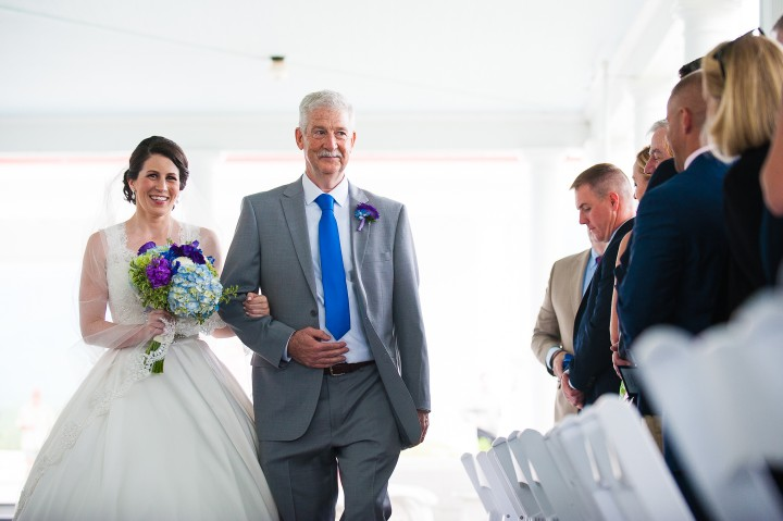 smiling bride and her dad walk down the  aisle during her mountain wedding ceremony