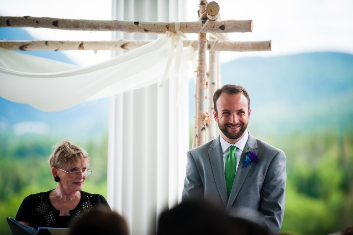 a very happy groom watches his bride walk down the aisle at the start of his luxury mountain wedding