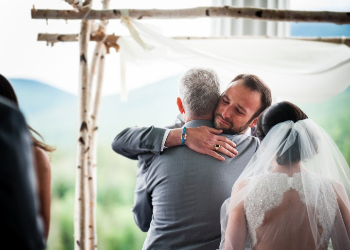handsome groom hugs the brides dad at the start  of his mountain wedding ceremony