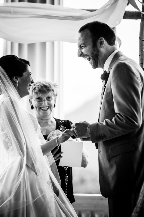 adorable bride and groom laugh while exchanging rings during their beautiful mountain ceremony
