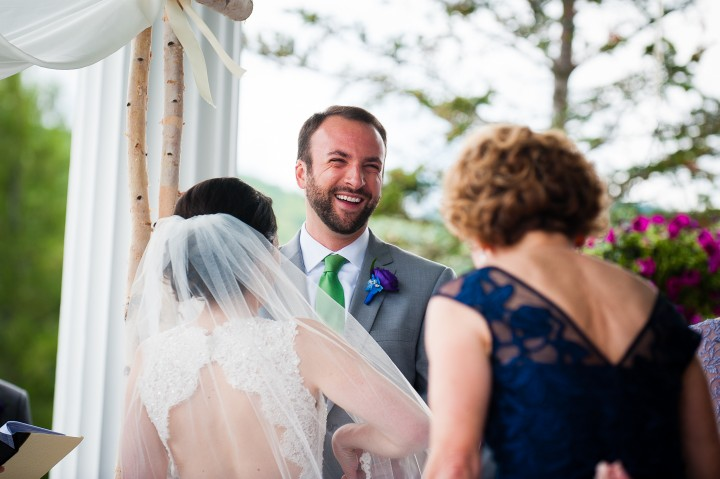 handsome groom smiling during his summertime mountain wedding