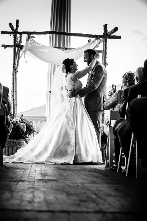 Black and white image of bride and groom smiling at each other just before their first kiss