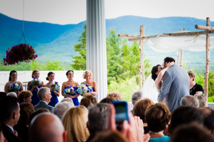 adorable bride and groom share their first kiss as husband and wife during their stunning mountain wedding