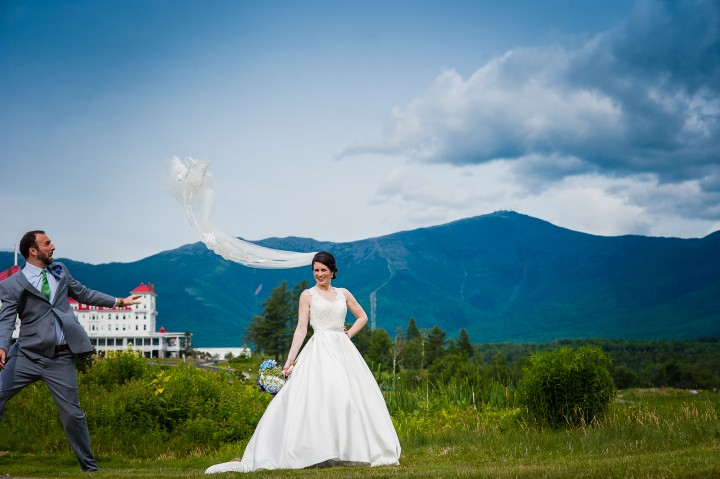 groom tosses brides veil in the air for a fun mountain bridal portrait