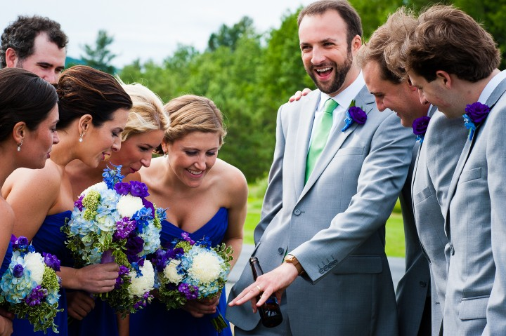 handsome groom shows off his wedding band to the wedding party