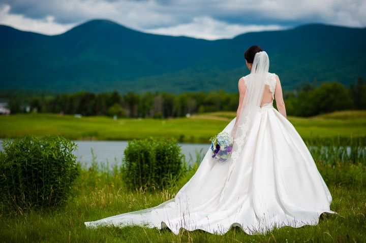 a gorgeous bride shows off the back of her stunning Stella York wedding gown during a mountain bridal portrait