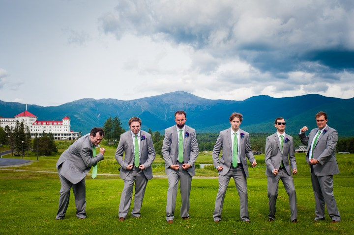 the handsome groom and his groomsmen goofing off during wedding wedding party pictures at the base of mount washington