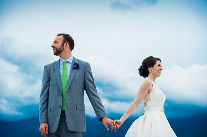 Bride and Groom hold hands with the sky and mountains behind them on their Mount Washington Wedding day