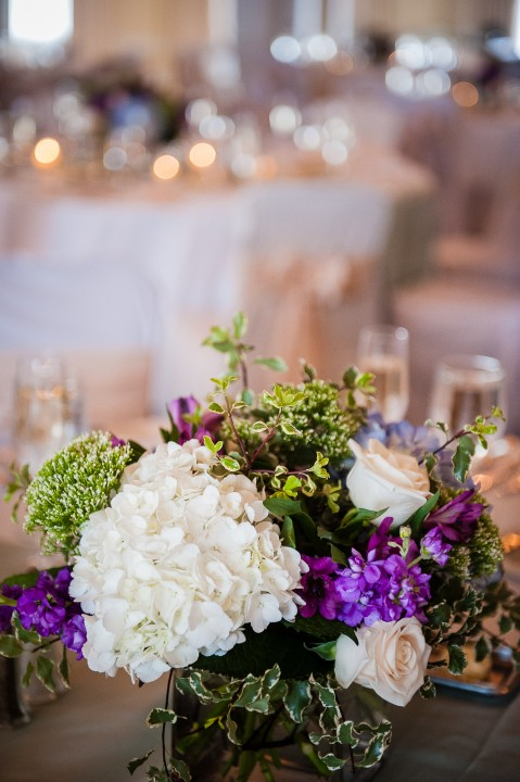 white and purple flowers adorned the circular tables during this summertime wedding reception