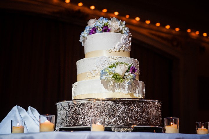 the traditional and very elegant white wedding cake was adorned with pretty purple green and white flowers
