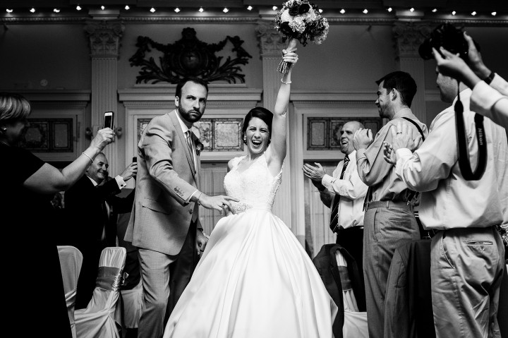 a very exuberant bride and groom cheer as they enter their wedding reception for their first dance as husband and wife