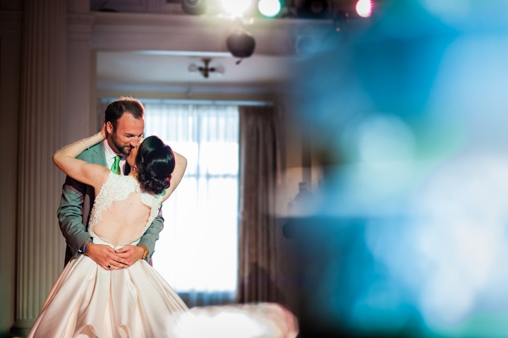 bride and groom embrace during their first dance as husband and wife during their gorgeous summertime wedding reception