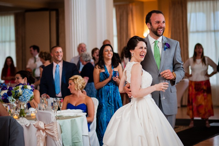 the adorable bride and groom laughing during one of the speeches at their fabulous wedding reception