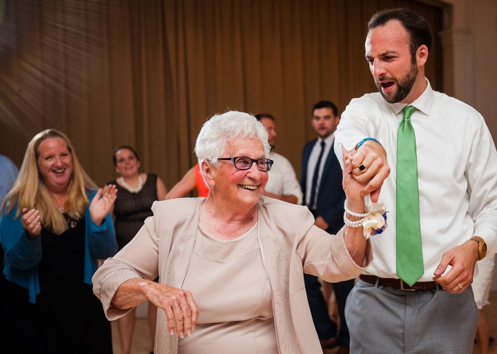 the groom dancing with the brides grandmother during a very fun wedding reception