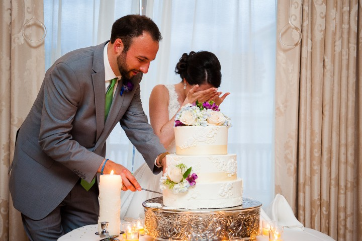 the bride covers her face as her groom attempts to cut the wedding cake during their mount washington hotel wedding reception