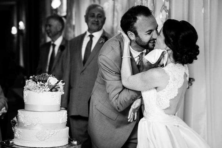the bride and groom share a post wedding cake cutting kiss during their fun mountain wedding reception