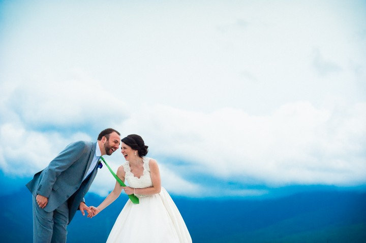 the bride and groom laugh hysterically after the bride grabs grooms tie during couples wedding portraits