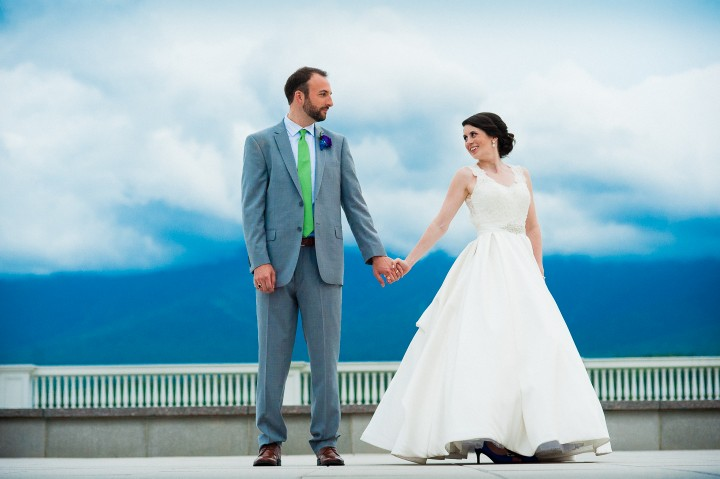 bride and groom holding hands for a wedding portrait on the mountain terrace of the mount washington hotel