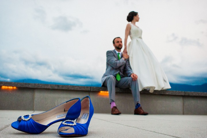 the brides beautiful blue wedding shoes in the foreground while the bride stands in the background with her handsome groom