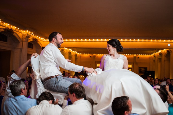 bride and groom laughing at each other during the always fun Hora during their summertime wedding reception