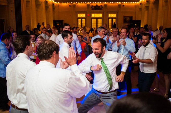 a very happy groom dancing with wedding guests during his fun wedding reception