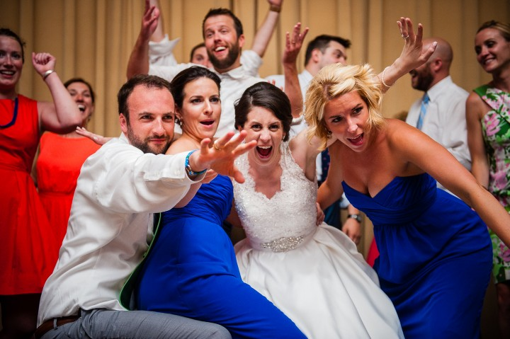 bride and groom with the brides two maid of honors being goofy during the wedding reception