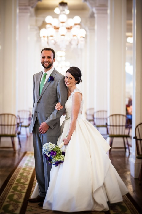 gorgeous bride and groom pose in the great hall inside the beautiful Omni Mount Washington Hotel during their wedding reception