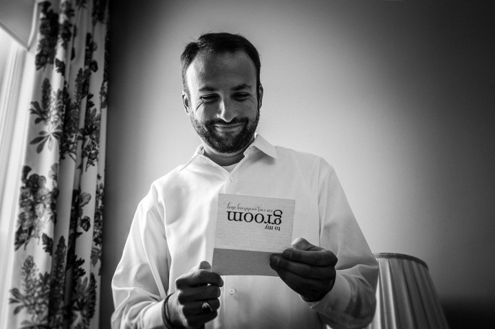 Groom smiling as he opens his wedding day present from his bride to be
