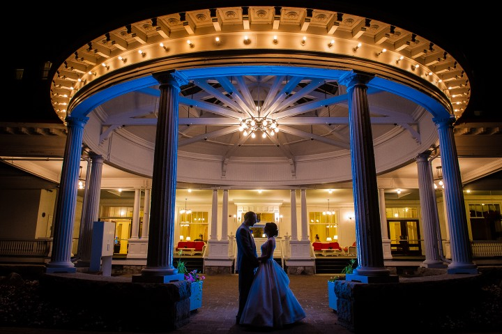bride and groom pose for an end of the night image in front of the gorgeous mount washington hotel